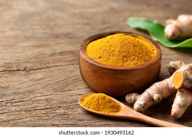 Turmeric (curcumin) powder in wooden bowl with fresh rhizome on wood background.