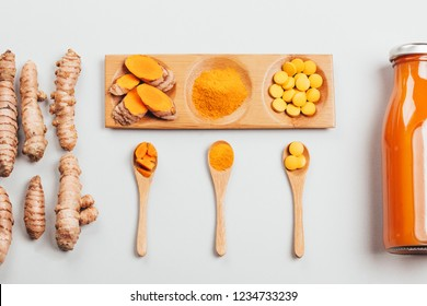 Turmeric in different conditions: fresh in bottle, pills, powder and cut plant on wooden tray. Flat lay style.
