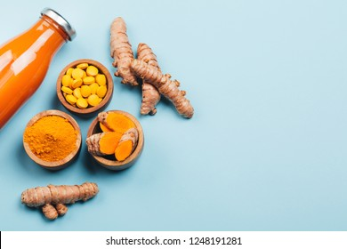 Turmeric in different conditions: fresh, dry root, pills, powder and cut plant on pastel blue background. Flat lay style. Place for text.