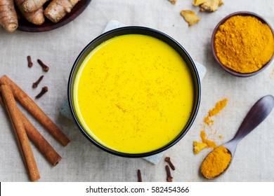 Turmeric drink, latte, tea, milk with cinnamon with fresh and dried turmeric on a textile grey background. Top view.