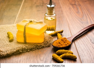 Turmeric essential oil with soap and dried Haldi sticks and powder in a wooden spoon