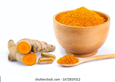 Turmeric ground in wooden bowl with curcuma root and tumeric powder capsule isolated on white  background. Natural medicine plant ,alternative medical health care and supplement concept .