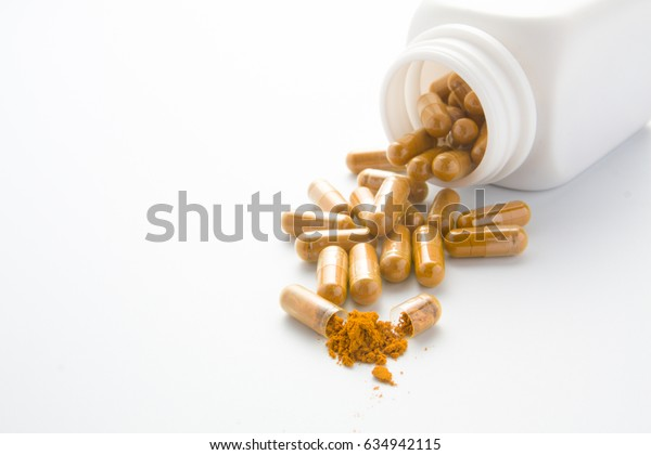 turmeric herb capsule from bottle on white background