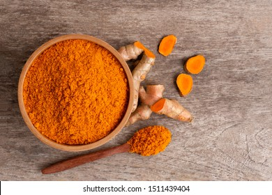 Turmeric ( known as curcumin, Curcuma longa Linn) powder in wooden bowl and rhizome isolated on old wood table background. Top view.