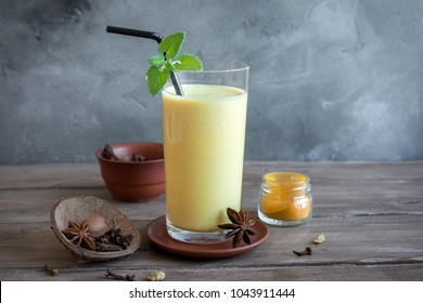 Turmeric Lassie or lassi in glass - Healthy Probiotic Indian cold drink made up of curd (yogurt), milk, spices and sugar. Turmeric Smoothie on wooden, copy space.