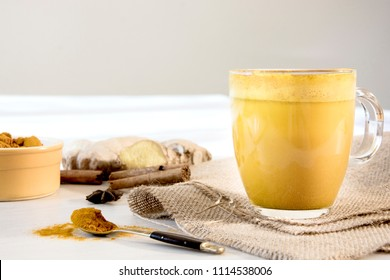 Turmeric latte in glass mug with yellow pot of turmeric in the background. Spoon, ginger, cinnamon and hessian fabric