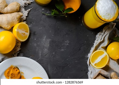 Turmeric latte or golden milk in glasses with ginger and lemons on a black  table. Copy space