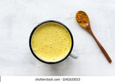 Turmeric latte, Golden milk. Hot  healthy drink. Concrete background. Top view.