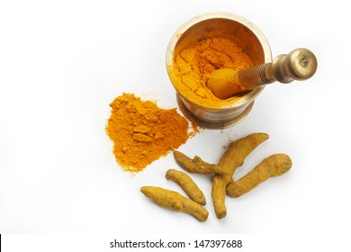 Turmeric and Turmeric Powder in an antique brass mortar isolated on a white background in full frame.