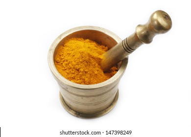 Turmeric Powder in an antique brass mortar isolated on a white background in full frame.