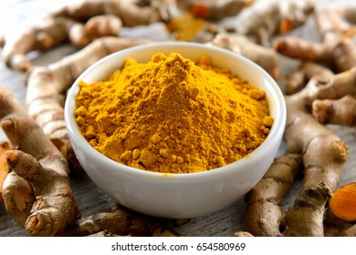 Turmeric powder and turmeric capsules on wooden background