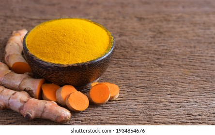 Turmeric powder and fresh turmeric (curcumin) on wooden background,Used for cooking,Natural dyes for fabric dyeing,copy space.