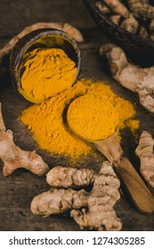 Turmeric powder and fresh turmeric on wooden background.
