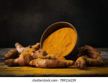Turmeric powder and fresh turmeric on wooden background.with copy space.