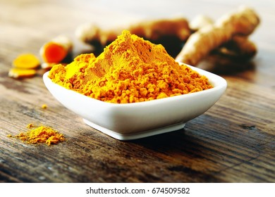 Turmeric powder and fresh turmeric roots on wooden background