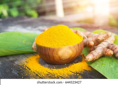 Turmeric powder and fresh turmeric in wooden bowls with green leaf on old wooden table. Herbs are native to Southeast Asia.