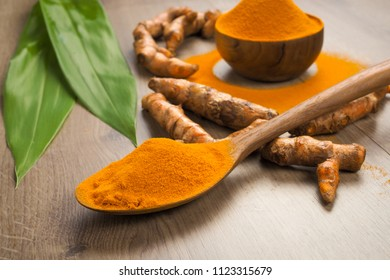 Turmeric powder and fresh turmeric in wooden spoon with green leaf on old wooden table. Herbs are native to Southeast Asia.