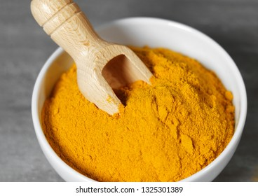 Turmeric powder healthy spice Asian food closeup of a white bowl with a wooden bailer.