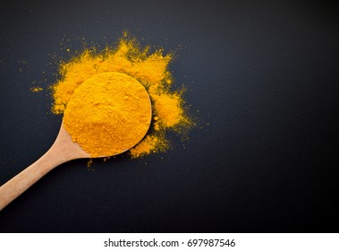 Turmeric powder on black background.