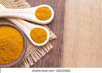 turmeric powder on wood background (curcuma longa)