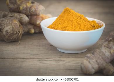 Turmeric powder and turmeric on wood desk