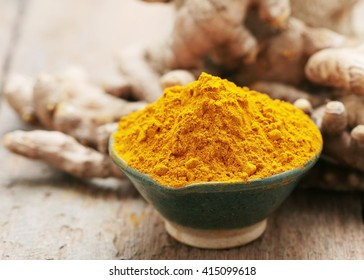 Turmeric powder and turmeric on wooden background.