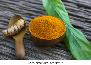 Turmeric powder on a wooden background.