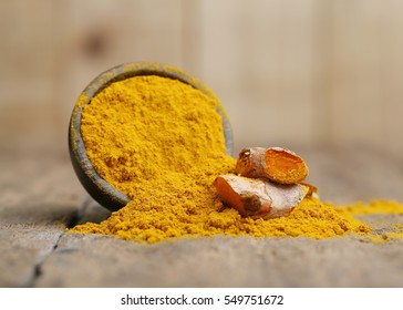 Turmeric powder on wooden background.