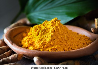 Turmeric powder on wooden background