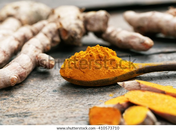 Turmeric powder and turmeric on wooden spoon.