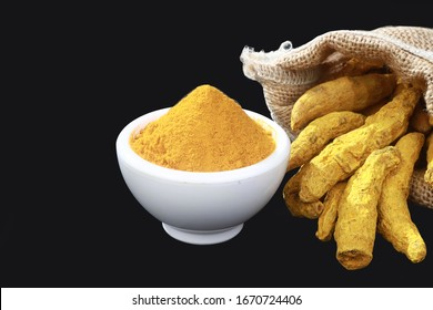 Turmeric powder placed in bowl with turmeric roots, group of Haldi and haldi gathi
