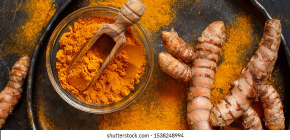 Turmeric powder and root on a dark background close up