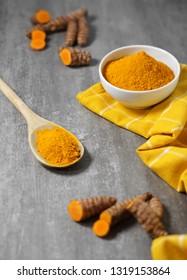Turmeric powder and roots healthy spice Asian food background with sliced turmeric roots and powder in a white bowl and a wooden spoon.