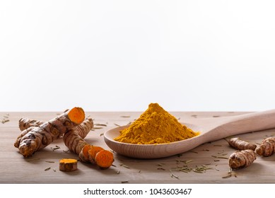 Turmeric powder and turmeric roots on a wooden surface with white background