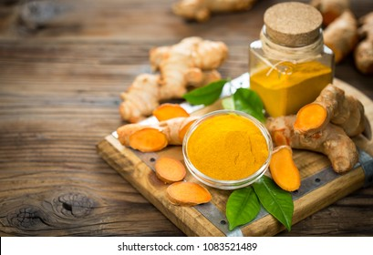 Turmeric powder and turmeric roots on the wooden table