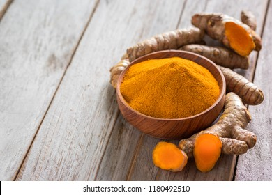 Turmeric powder and roots on wooden background, asian herb for medication