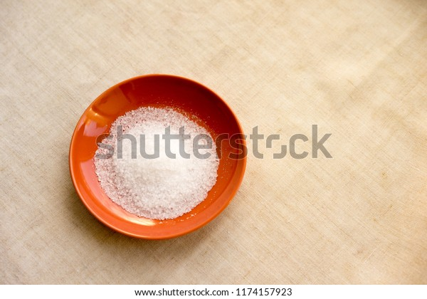Turmeric powder and salt in red bowl over fabric background