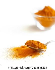 Turmeric powder with a spon isolated on white close up