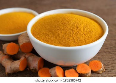 Turmeric powder in a white bowl and fresh turmeric (curcumin) on wooden background,For cooking and for herbs.