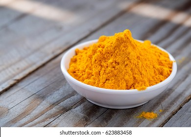 Turmeric powder in white cup on wooden floor.