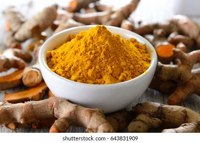 Turmeric powder in white cup on wooden floor