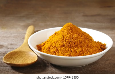 turmeric powder in white dish on wooden background