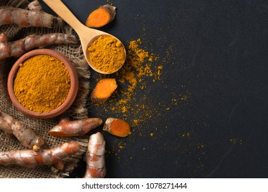 turmeric powder in wood spoon with turmeric root on black table, spices and herb concept