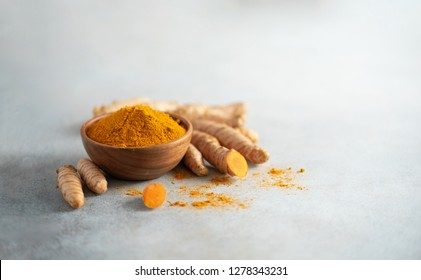Turmeric powder in wooden bowl and fresh turmeric root on grey concrete background. Banner with copy space.