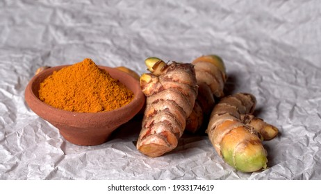 Turmeric powder in wooden bowl and fresh turmeric root on textured background. Herbs are native ,Food and drink, diet nutrition, health care concept.