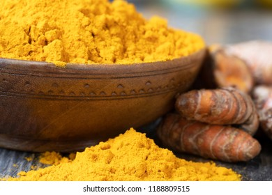 Turmeric powder in a wooden bowl and on the table with turmeric roots.