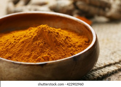 Turmeric powder in wooden bowl on wooden.
