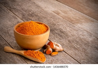 Turmeric powder in wooden bowl and spoon with tumeric ground root (known as Curcumin, Curcuma longa Linn) isolated on old wood table background. Copyspace for text and content.