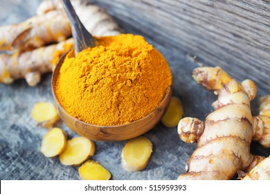 Turmeric powder in wooden bowls on wooden table. herbal
