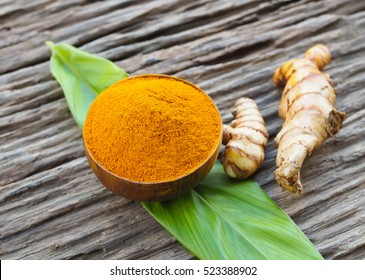Turmeric powder in wooden bowls on old wooden table. Herbs are native to Southeast Asia.